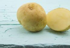 Fermez-vous d'une pomme de terre et découpez en tranches sur le backgr rustique en bois de vert de mer Photos stock