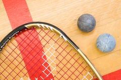 Fermez-vous d'une raquette et d'une boule de courge sur le fond en bois Images stock