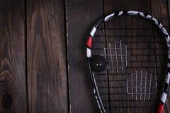 Fermez-vous d'une raquette et d'une boule de courge sur le fond en bois Photographie stock