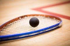 Fermez-vous d'une raquette et d'une boule de courge au-dessus de fond en bois Images libres de droits