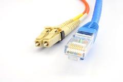 Fermez-vous d'une tête de tête optique de patchcord de fibre et de câble LAN d'UTP Photo libre de droits