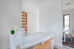 Fermez-vous d'une table blanche qui a des tiroirs sous lui Image stock