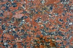 Fermez-vous d'une texture polie de granit marbrée par rouge Photos stock