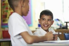 Fermez-vous de deux écoliers primaires agissant l'un sur l'autre dans la classe images libres de droits