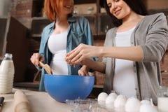 Fermez-vous de deux amis faisant cuire des gâteaux Photo stock