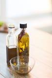 Fermez-vous de deux bouteilles d'huile d'olive et cuvettes d'huile Photo libre de droits