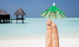 Fermez-vous de deux doigts avec le parapluie de cocktail Photo stock