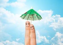 Fermez-vous de deux doigts avec le parapluie de cocktail Photographie stock libre de droits