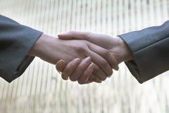 Fermez-vous de deux gens d'affaires se serrant la main par le World Trade Center des Chine dans Pékin Photographie stock