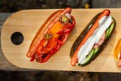 Fermez-vous de deux hot-dogs sur le hachoir en bois photos stock