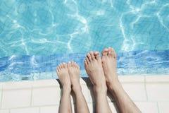 Fermez-vous de deux jambes des personnes par le côté de piscine Photo libre de droits