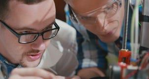 Fermez-vous de deux jeunes étudiants observant la création du robot banque de vidéos