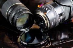 Fermez-vous de deux objectifs de caméra avec le filtre circulaire d'isolement sur des bandes de film négatif photos stock