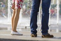 Fermez-vous de deux paires de jambes, fille dans la robe courte avec le modèle floral et chaussures et homme blancs dans les blue Photographie stock libre de droits