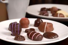 Fermez-vous de deux plats des chocolats avec une tasse de chocolat chaud photos stock