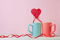 Fermez-vous de deux tasses et lolipop ou bonbon dur en forme de coeur sur la table Fond rose Place pour le texte Copyspace ` S de Photo libre de droits