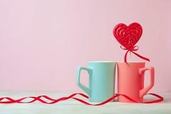 Fermez-vous de deux tasses et lolipop ou bonbon dur en forme de coeur sur la table Fond rose Place pour le texte Copyspace ` S de Photos libres de droits