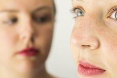Fermez-vous de deux visages de jeunes filles Photographie stock libre de droits