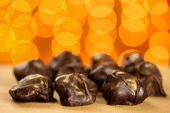 Fermez-vous de frais, délicieux et les bonbons crus faits maison sains de chocolat avec d'or arrose sur le fond brouillé orange photo stock