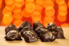 Fermez-vous de frais, délicieux et les bonbons crus faits maison sains de chocolat avec d'or arrose sur le fond brouillé rouge av image libre de droits