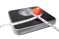 Fermez-vous de l'échelle, de la bande et de la pomme d'isolement sur le blanc Photos stock