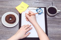 Fermez-vous de l'écriture de main du ` s d'étudiant en bloc-notes, en faisant des notes, liste, astuces, écriture, le temps suiva photos libres de droits