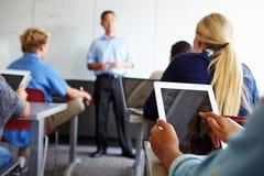 Fermez-vous de l'élève à l'aide de la Tablette de Digital dans la salle de classe Image stock