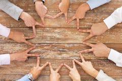 Fermez-vous de l'équipe d'affaires montrant le geste de victoire Photographie stock libre de droits