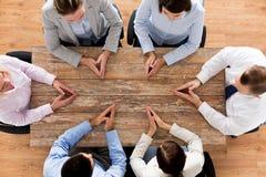 Fermez-vous de l'équipe d'affaires s'asseyant à la table Photos stock