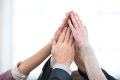 Fermez-vous de l'équipe d'affaires tenant des mains sur des mains Photographie stock