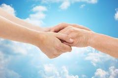 Fermez-vous de l'aîné et de la jeune femme tenant des mains Image stock