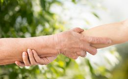 Fermez-vous de l'aîné et de la jeune femme tenant des mains Images libres de droits