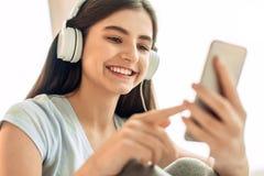 Fermez-vous de l'adolescente choisissant des voies de musique Photo stock