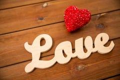 Fermez-vous de l'amour de mot avec la décoration rouge de coeur Photographie stock