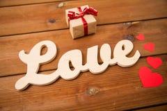 Fermez-vous de l'amour de mot avec le boîte-cadeau et les coeurs rouges Photographie stock libre de droits