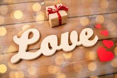 Fermez-vous de l'amour de mot avec le boîte-cadeau et les coeurs rouges Photo stock