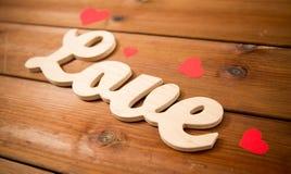 Fermez-vous de l'amour de mot avec les coeurs de papier rouges Photos stock