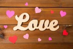 Fermez-vous de l'amour de mot avec les coeurs de papier rouges Photo stock