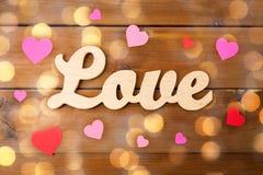 Fermez-vous de l'amour de mot avec les coeurs de papier rouges Images stock