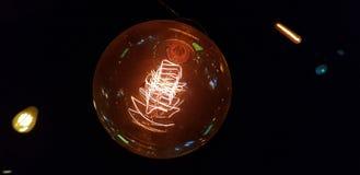 Fermez-vous de l'ampoule électrique jaune dans l'environnement foncé photo stock