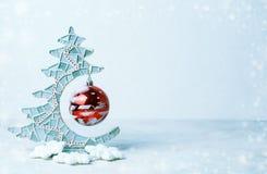 Fermez-vous de l'arbre de Noël décoratif et de la boule en verre de Noël rouge Couleurs froides, neige Copiez l'espace, le placez Images stock