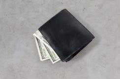 Fermez-vous de l'argent du dollar dans le portefeuille noir sur la table Photographie stock libre de droits