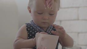 Fermez-vous de l'enfant jouant avec les pâtes tandis que les mains de sa mère l'aidant Jeune femme pr?parant la nourriture dans l banque de vidéos