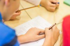 Fermez-vous de l'essai d'écriture d'écolier à l'école Image stock