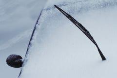 Fermez-vous de l'essuie-glace augmenté par noir de voiture couvert dans la neige Photo stock