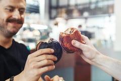 Fermez-vous de l'hamburger clincing de jeune homme bel au café avec l'ami et le sourire photos stock