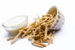 Fermez-vous de l'herbe Satavari d'Ayurvedic ou du kurilo ou du racemosus d'asperge d'isolement sur le blanc dans un bol en verre  photos stock