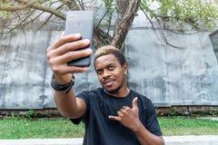 Fermez-vous de l'homme à la peau foncée dans le T-shirt noir faisant le selfie au téléphone portable photographie stock