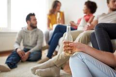 Fermez-vous de l'homme avec la bouteille et les amis à bière Photographie stock