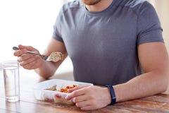 Fermez-vous de l'homme avec la fourchette et arrosez manger de la nourriture Photos stock